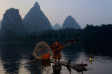 Fisherman with cormorant on pole on the Li river Yangshuo China with tall karst limestone peaks at dawn