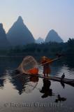 Cormorant fisherman polling down the Li river Yangshuo China with tall karst limestone peaks at dawn