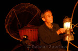 Cormorant fisherman lifting his lamp on his raft in early morning darkness on the Li river Yangshuo China