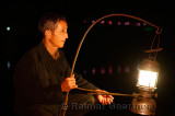 Cormorant fisherman placing his lamp on his raft in early morning darkness on the Li river Yangshuo China