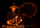 Cormorant fisherman lighting his lamp in early morning darkness on the Li river Yangshuo China