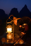 Chinese cormorant fisherman holding a bird on a bamboo raft with lantern at dawn on the Li river Yangshuo China