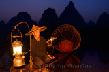 Fisherman holding cormorant on bamboo raft with lantern basket and net at dawn on the Li river Yangshuo China