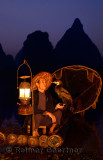 Fisherman looking at cormorant on bamboo raft with lantern and net at dawn on the Li river Yangshuo China
