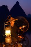Chinese cormorant fisherman holding his bird at dawn on the Li river Yangshuo China