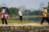 Chinese women walking on stone bridge at Fuli Li river inlet with karst mountain peaks China