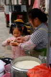 Street vendor giving fresh curd Douhua to a young school girl in Fuli China