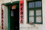Duilian scrolls of poetry hanging outside a green door in Fuli China