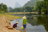 Chinese women washing vegetables in pond water at Fuli Li river inlet with karst mountain peaks China