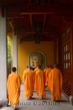 Buddhist monks in orange robes congregating at the dining hall of the Ling Yin Temple in Hangzhou China