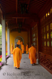 Buddhist monks in orange robes called to the dining hall of the Ling Yin Temple in Hangzhou China