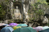 Limestone Buddha scultpures at Feilai Feng in the rain with umbrellas Ling Yin temple Hangzhou China
