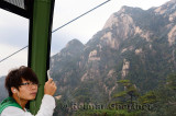 Young man taking a cellphone picture of Yellow Mountain from the Yungu cable car China
