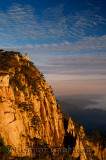 Visitor on Lion Peak at sunrise with fog in valley at Huangshan Mountain China