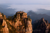 Red light on Monkey watching the Sea Peak at dawn with fog in valley at Huangshan China