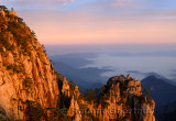 Lion Peak and Stone Monkey watching the Sea Peak at first light with fog in valley at Huangshan Mountains China