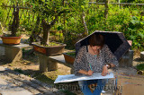 Female student artist drawing in the garden of a farm house in Hongcun village in China