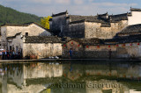 Ancient buildings with geese and tourists reflected in the still Half moon pond in Hongcun village China