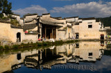 White buildings reflected in the still Half moon pond in the ancient village of Hongcun China