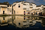 Ancient white buildings reflected in the still Half moon pond in Hongcun village China