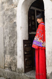 Profile of a new bride wearing her red wedding dress in the doorway of an ancient Hongcun village building China
