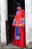 Young bride wearing her red wedding dress in the doorway of a Hongcun village building China