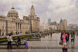 Tourists walking on a wet Bund after a rainstorm with old buildings in Shanghai China