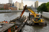 Excavator and barge dredging the Wusong river at the Waibaidu bridge Shanghai China