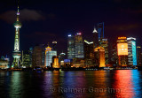 Bright lights of Pudong high rise towers at night reflected in the Huangpu river Shanghai China