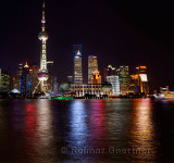 Bright night lights of Pudong high rise towers reflected in the Huangpu river with boats Shanghai China