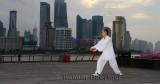 Tai Chi sword master in white and kite flyer on the Bund with Pudong high rise towers in the morning Shanghai China