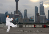 Tai Chi sword master and kite flyer on the Bund with Pudong high rise towers in the morning Shanghai China