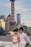 Wedding couple in white on the Bund with Pudong high rise towers Shanghai China