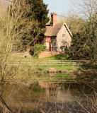 Rural  cottage  reflected  in  pond.