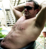 handsome man lounging poolside suntanning bathing soaking daddy.jpg