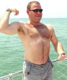 very hairy daddy bear flexing big muscles on boat.jpg