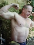 older cowboy hunk daddie flexing muscles barn.jpg