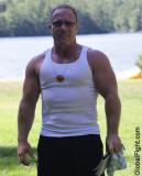 massively large biceps bulging muscles man in park.jpg
