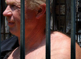 caged prisoner man undressing hairy shoulders.jpg