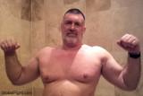 older hunky musclebear flexing big arms.jpg
