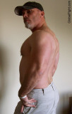 muscleman wearing baseballcap posing flexing big arms.jpg