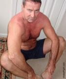 very hairy legs man sitting floor stretching exercises.jpg