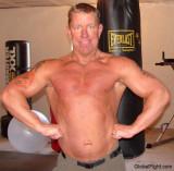 boxing bag gym gay man posing flexing arms.jpg