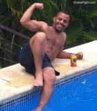 muscular hot black dude flexing biceps poolside.jpg