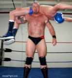 big brutish man lifting wrestler overhead backbreaker application.jpg