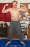 guy posing sweat pants wrestling mats flexing arms biceps.jpg