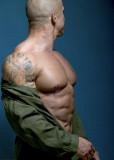 muscleman removing shirt tattoos on arm bicep.jpg