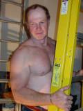 man working shirtless carrying ladder construction.jpg