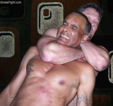 tanned older surfer daddy being choked wrestling hold.jpg