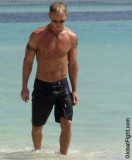 studly muscled ripped jock walking on beach.jpg